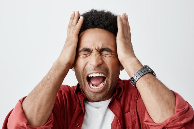 Homem gritando de enxaqueca. feche o retrato do cara infeliz de pecado preto com penteado afro em camiseta branca sob camisa casual vermelha, apertando a cabeça com as mãos da dor de cabeça. Foto gratuita