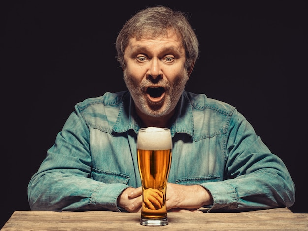 Homem gritando na camisa jeans com copo de cerveja Foto gratuita