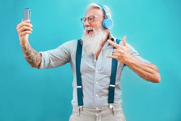Homem hipster sênior usando o aplicativo de smartphone para criar lista de reprodução com música rock Foto Premium