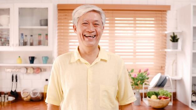 Homem idoso asiático que sente feliz sorrindo e olhando à câmera quando relaxe na cozinha em casa. Foto gratuita