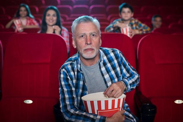 Homem idoso assistindo filme no cinema Foto gratuita
