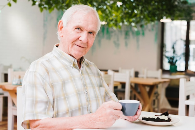 Homem idoso, bebendo, chá, e, olhando câmera Foto gratuita