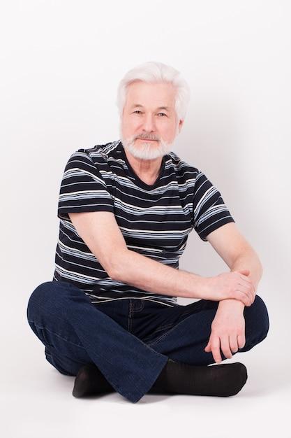 Homem idoso bonito sentado Foto gratuita