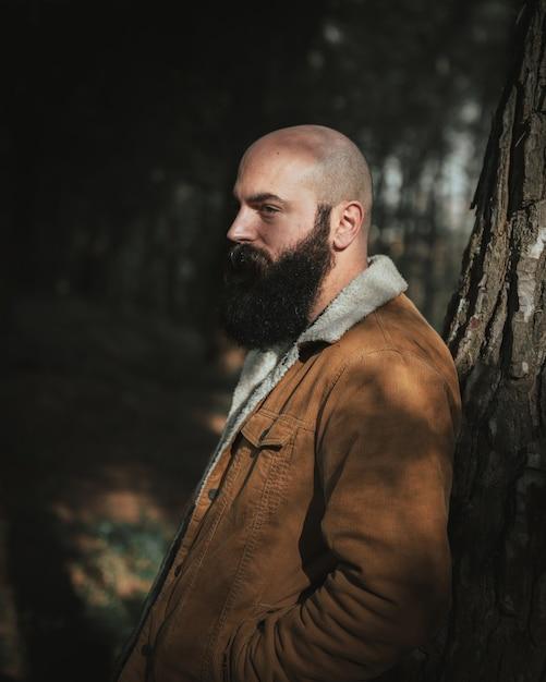 Homem idoso careca com um bigode denso e preto no parque encostado em uma árvore Foto gratuita