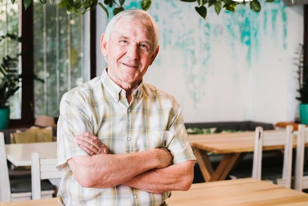 Homem idoso, com, braços cruzados, olhando câmera Foto gratuita
