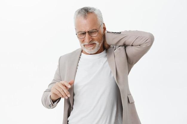 Homem idoso com problemas de terno, reclamando de dor nas costas, tocando o pescoço Foto gratuita