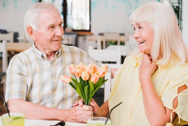 Homem idoso, dar, flores, para, amado Foto gratuita
