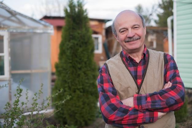Homem idoso de colete no fundo da casa na aldeia Foto Premium