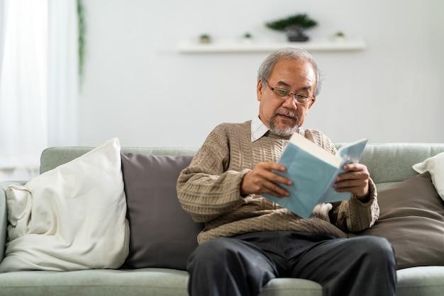Homem idoso feliz aposentadoria asiática sentado no sofá na sala lendo um livro de ficção. Foto Premium