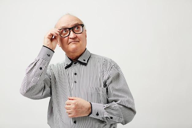 Homem idoso pensativo em copos Foto gratuita