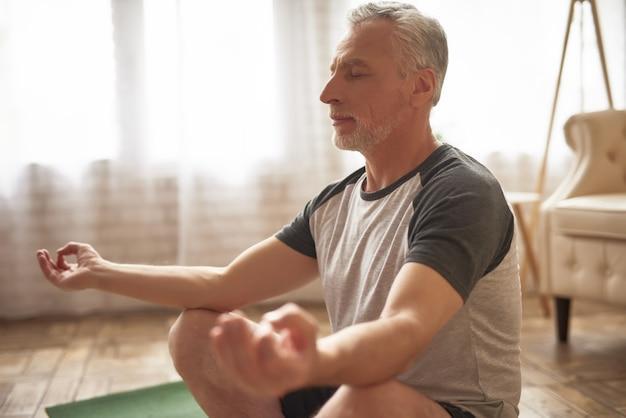 Homem idoso que medita em casa o relevo de tensão. Foto Premium