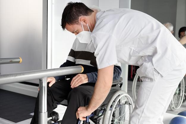 Homem idoso sendo assistido por um fisioterapeuta no centro de reabilitação. Foto Premium