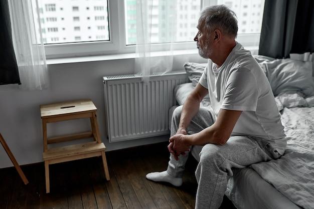 Homem idoso sentado sozinho em casa, distanciamento social e auto-isolamento em bloqueio de quarentena por coronavírus Foto Premium