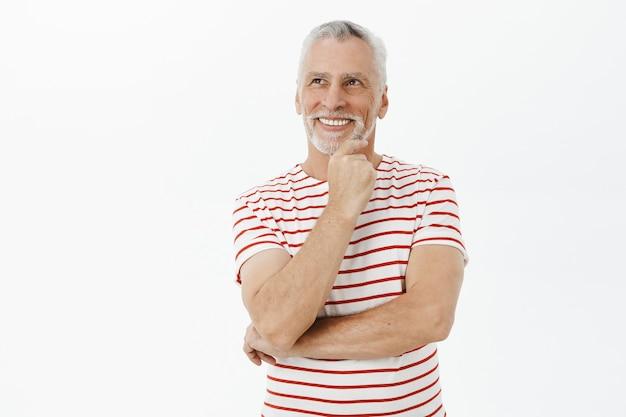 Homem idoso sorridente e pensativo, olhando no canto superior esquerdo com uma expressão satisfeita Foto gratuita