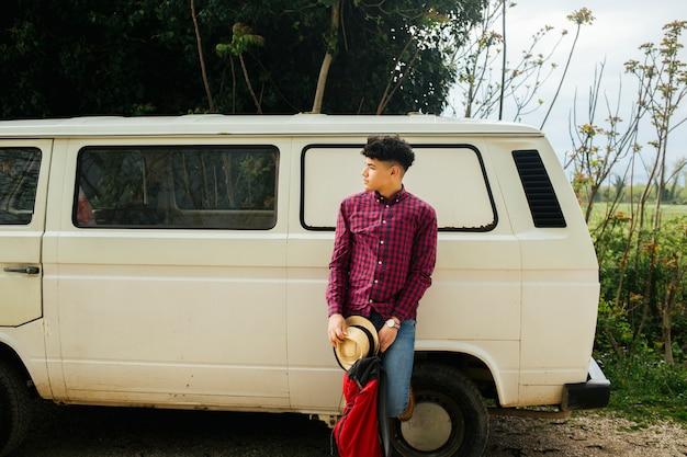 Homem, inclinar-se, furgão, segurando, chapéu, e, mochila, olhando Foto gratuita