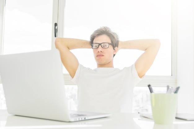 Homem, inclinar-se trás, em, seu, cadeira, olhar, laptop, ligado, tabela Foto gratuita