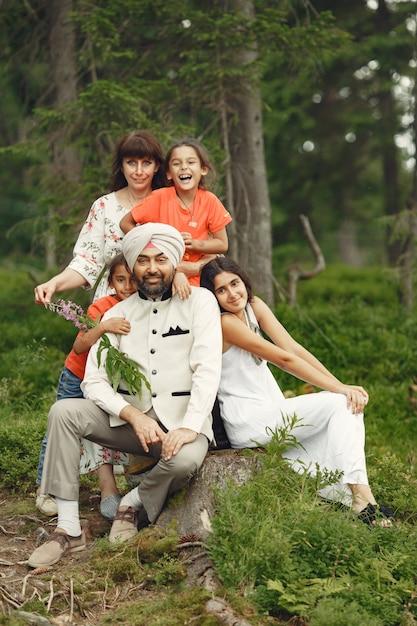 Homem indiano em uma floresta. macho em um turbante tradicional. família internacional em uma floresta de verão. Foto gratuita