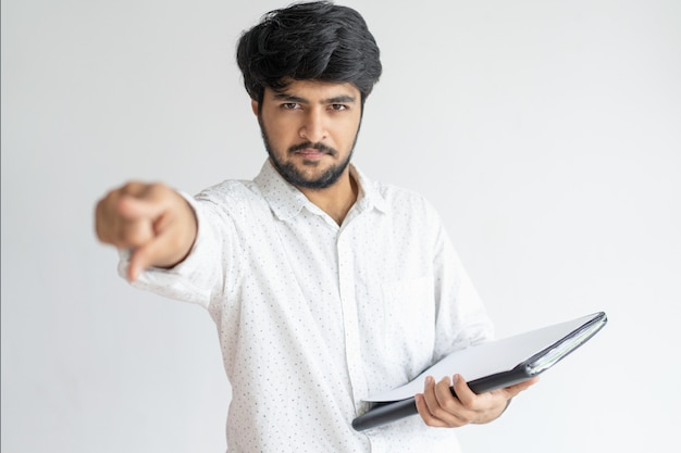 Homem indiano sério apontando para você e segurando documentos Foto gratuita