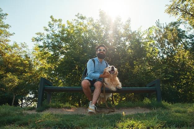 Homem interessante sentado com seu cachorro na cadeira no parque Foto gratuita