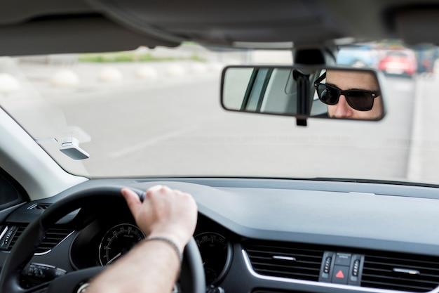 Homem irreconhecível, andar de carro na estrada movimentada Foto gratuita