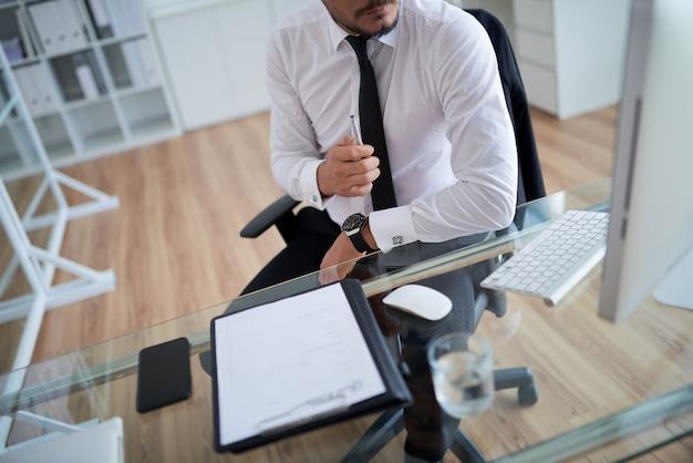 Homem irreconhecível de camisa formal e gravata trabalhando no escritório Foto gratuita