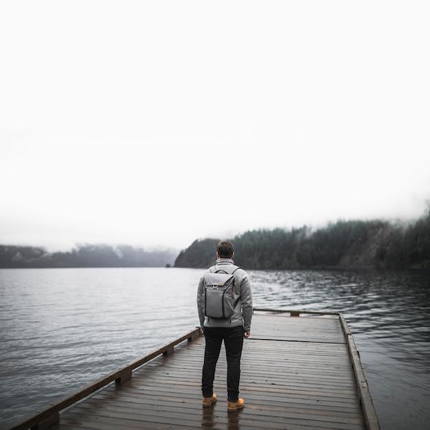 Homem irreconhecível no cais de madeira Foto Premium