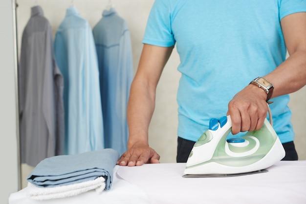 Homem irreconhecível passando camisas e roupa em casa Foto gratuita