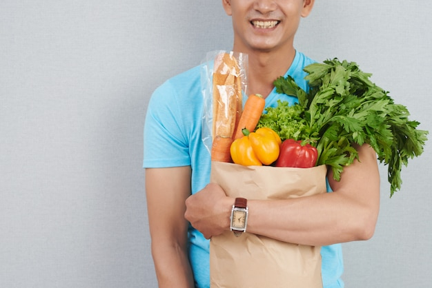 Homem irreconhecível, posando com saco de papel cheio de legumes frescos, ervas verdes e baguete Foto gratuita