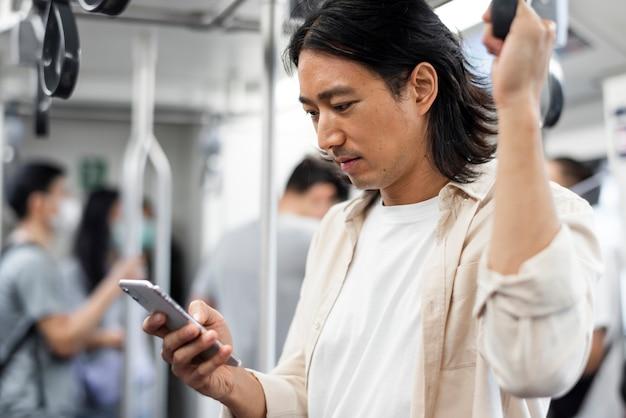Homem japonês navegando em seu telefone enquanto está no trem Foto gratuita