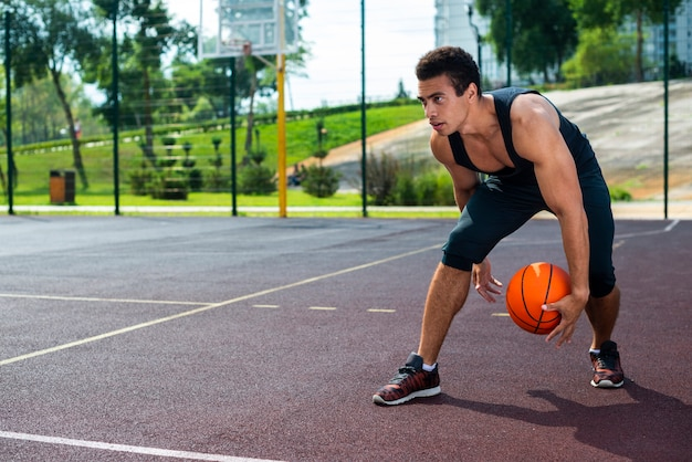 Homem jogando basquete na quadra do parque Foto gratuita
