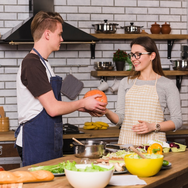 Homem jovem, abóbora entrega, para, namorada, em, cozinha Foto gratuita