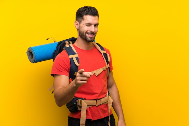 Homem jovem alpinista aponta o dedo para você Foto Premium