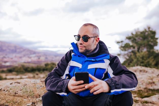 Homem jovem alpinista usando telefone inteligente no topo da montanha. dia nublado Foto Premium