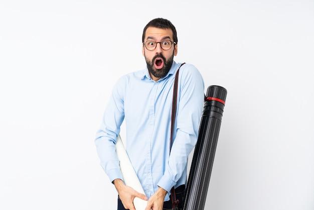 Homem jovem arquiteto com barba sobre parede branca isolada com expressão facial de surpresa Foto Premium