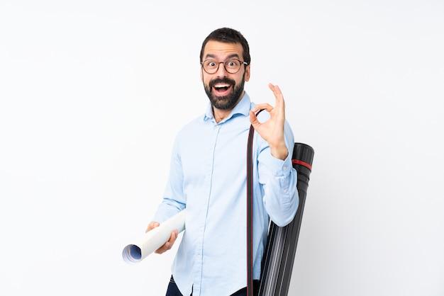 Homem jovem arquiteto com barba sobre parede branca isolada surpreso e mostrando sinal okey Foto Premium
