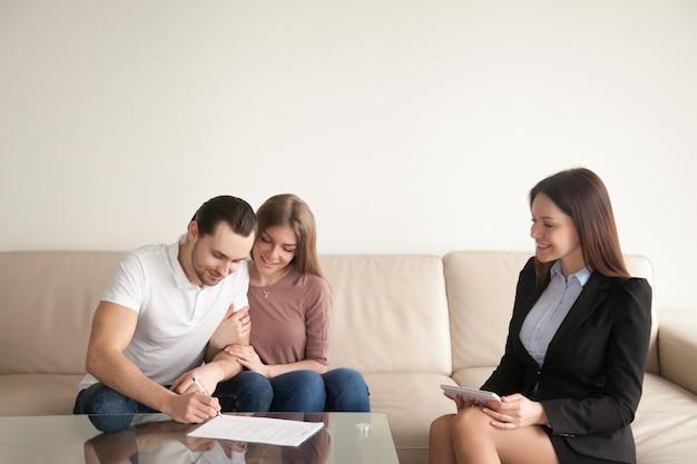 Homem jovem, assinando, papeis, sentando, perto, esposa, e, corretor de imóveis Foto gratuita