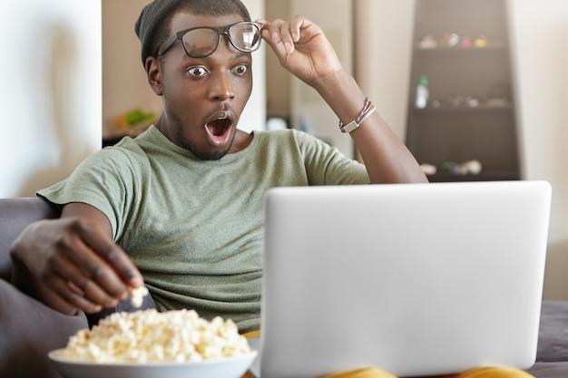 Homem jovem atordoado tirando os óculos de espanto enquanto assiste a séries policiais online no laptop Foto gratuita