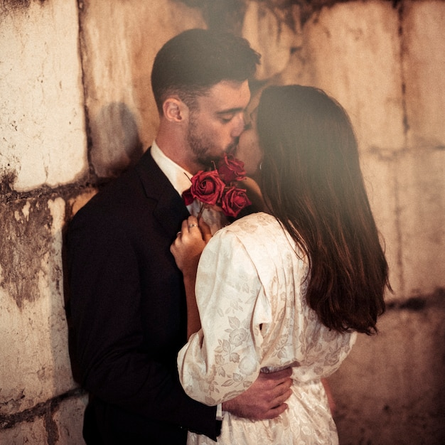 Homem jovem, beijando, mulher, inclinar-se, parede Foto gratuita