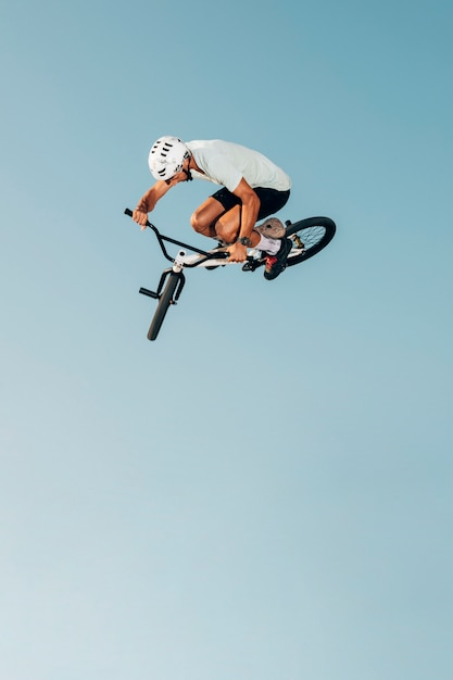 Homem jovem, bicicleta, pular, vista baixa ângulo Foto gratuita
