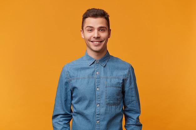 Homem jovem bonito e atraente, sorrindo delicadamente vestido com uma linda camisa jeans isolada em uma parede amarela Foto gratuita