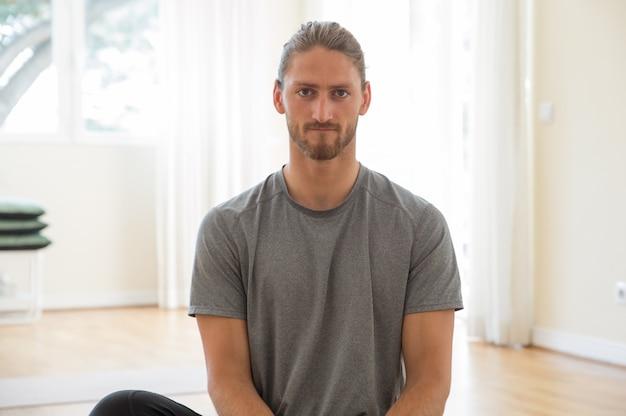 Homem jovem bonito sério posando no ginásio Foto gratuita