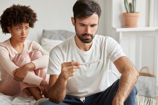 Homem jovem com a barba por fazer descontente realiza teste de gravidez, sente-se estressado com resultados positivos e espera um bebê indesejado. mulher descontente se senta atrás. Foto gratuita