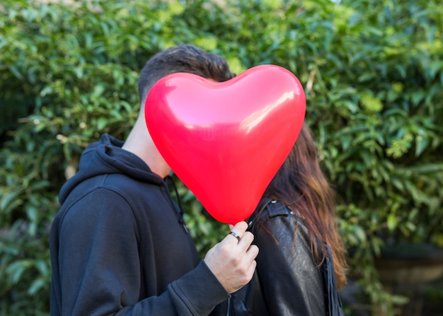 Homem jovem, com, balloon, em, forma, de, coração, beijando, mulher Foto gratuita