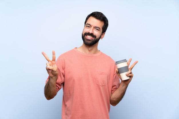 Homem jovem, com, barba, segurando, um, levar, café, ligado, azul, mostrando, sinal vitória, com, ambos, mãos Foto Premium