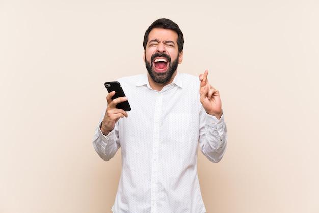Homem jovem, com, barba, segurando, um, móvel, com, dedos cruzando Foto Premium