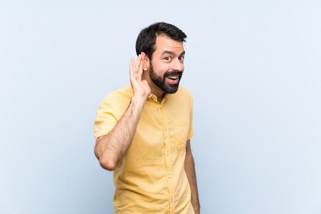 Homem jovem, com, barba, sobre, isolado, azul, escutar, algo, pondo mão, ligado, a, orelha Foto Premium