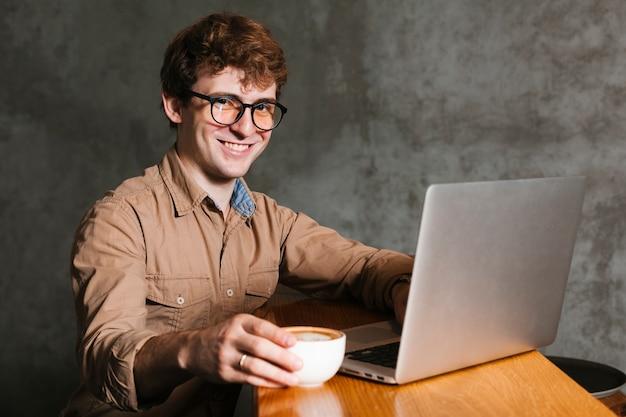 Homem jovem, com, laptop, sorrindo Foto gratuita