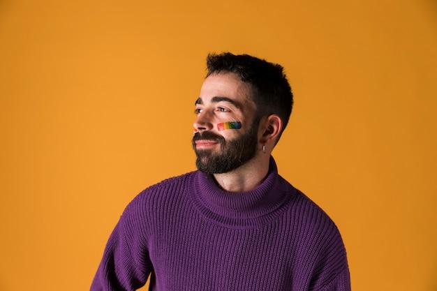 Homem jovem, com, lgbt, arco íris, bandeira, ligado, rosto Foto gratuita