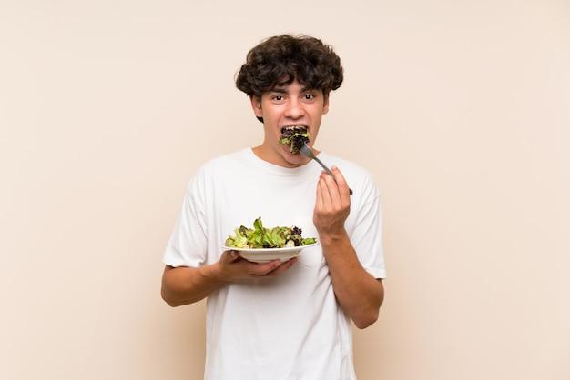 Homem jovem, com, salada, sobre, isolado, parede verde Foto Premium