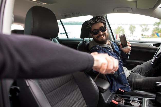 Homem jovem, com, telefone, saudação, amigo, enquanto, sentando carro Foto gratuita